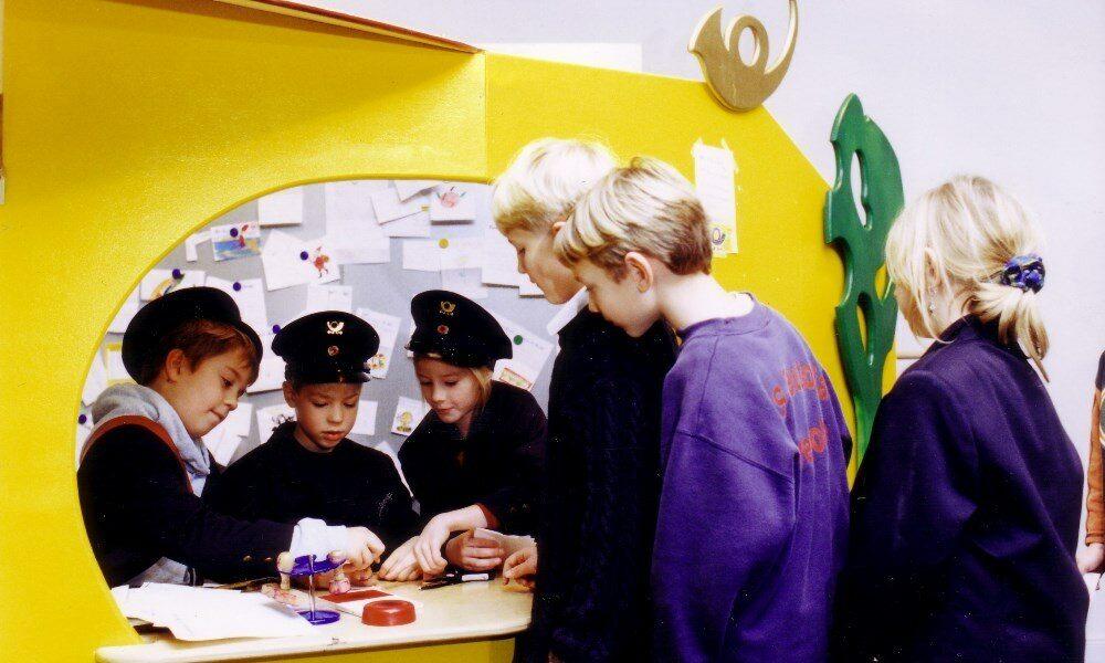Kinder stehen am Schalter der Kinderpost an, um ihre Brief einzureichen, während hinter dem gelben Schalter die Kinder in Uniformen die Post annehmen und stempeln.
