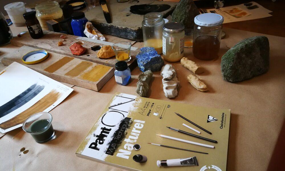 Auf einem mit Packpapier geschütztem Arbeitsplatz liegen Steine, Naturmaterialien und Behältnisse mit geriebenen Substanzen, die zur Herstellung von Farben genutzt werden können. Im Vordergrund liegt das Buch Paint on Naturel. Auf einem Stück Karton sind Farbbeispiele zu sehen.