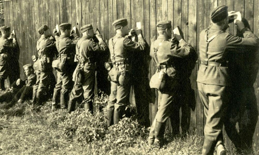 Eine Reihe von Soldaten aus dem 2. Weltkrieg sind von hinten zu sehen. Sie stehen an einer Holzwand aus Latten und schreiben Postkarten. Die Holzwand dient als Schreibunterfläche.