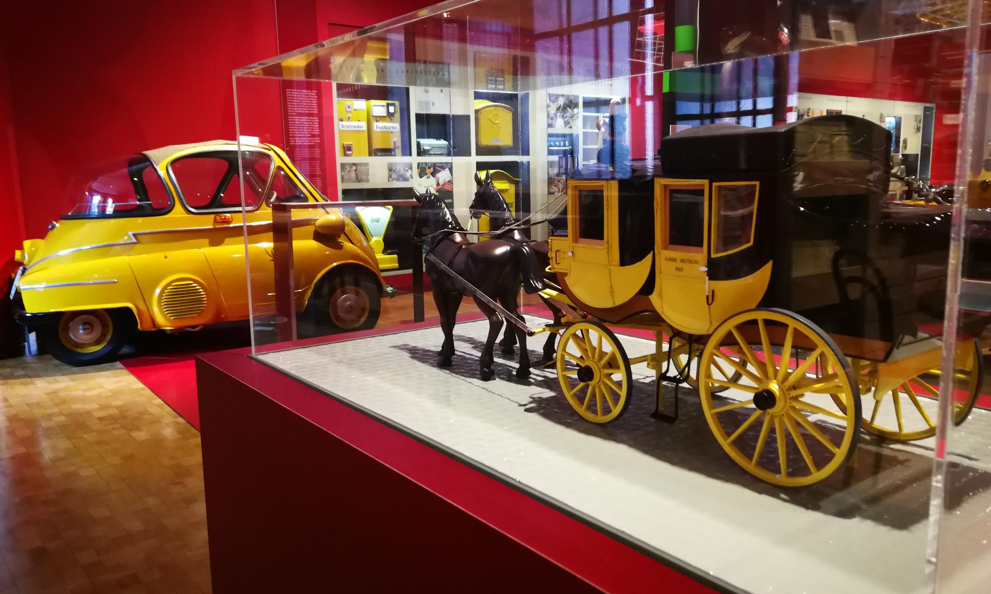 """Verlinkung zur Seite """"Unser Programm"""" Auf dem Bild ist zu sehen: Blick in die Dauerausstellung des Museums für Kommunikation. Im Vordergrund ein Modell der historischen Postkutsche des Typs Berline. Im Hintergrund eine gelbe Original Post-Isetta."""
