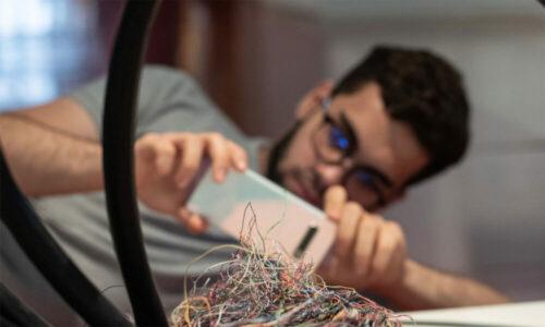 Museum für Kommunikation bietet verschiedene digitale Angebote. Auf dem bild ist verschwommen ein junger Mann zu sehen, der ein Knäuel von Kabel mit seinem Smartphone fotografiert.