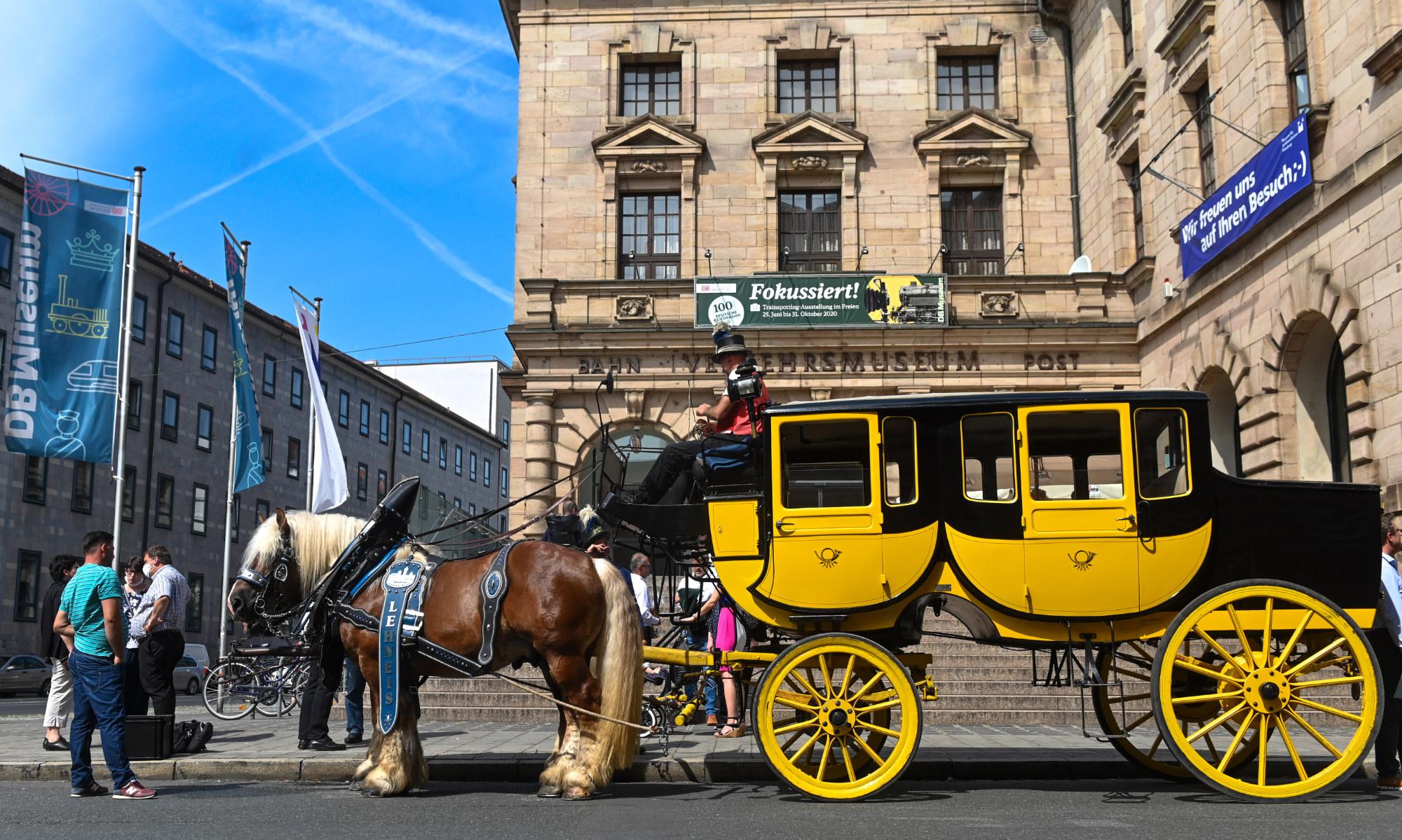 Eine große doppeltürige Postkutsche des Typs Berline steht vor dem Haupteingang des Museums für Kommunikation Seiten und Reifen sind in dem typischen Gelb der Post lackiert, Dach und Gepäckraum sind schwarz.