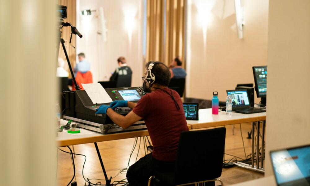 Digitales Live-Event im Festsaal. Im Vordergrund bedient ein Tontechniker das Mischpult. Im Hintergrund sitzen Zuschauer:innen.