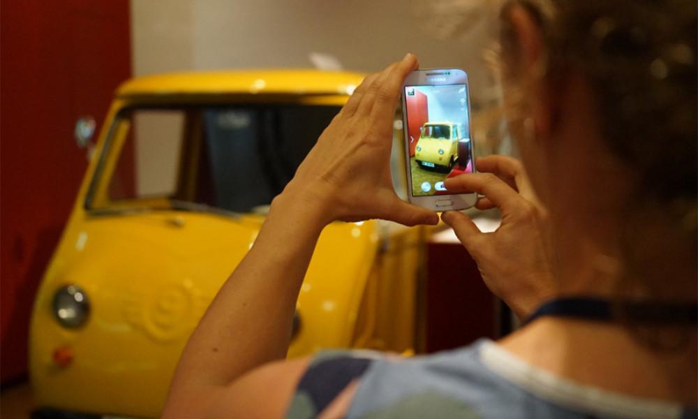 Eine Frau fotografiert die gelbe Post Isetta im Museum für Kommunikation Nürnberg